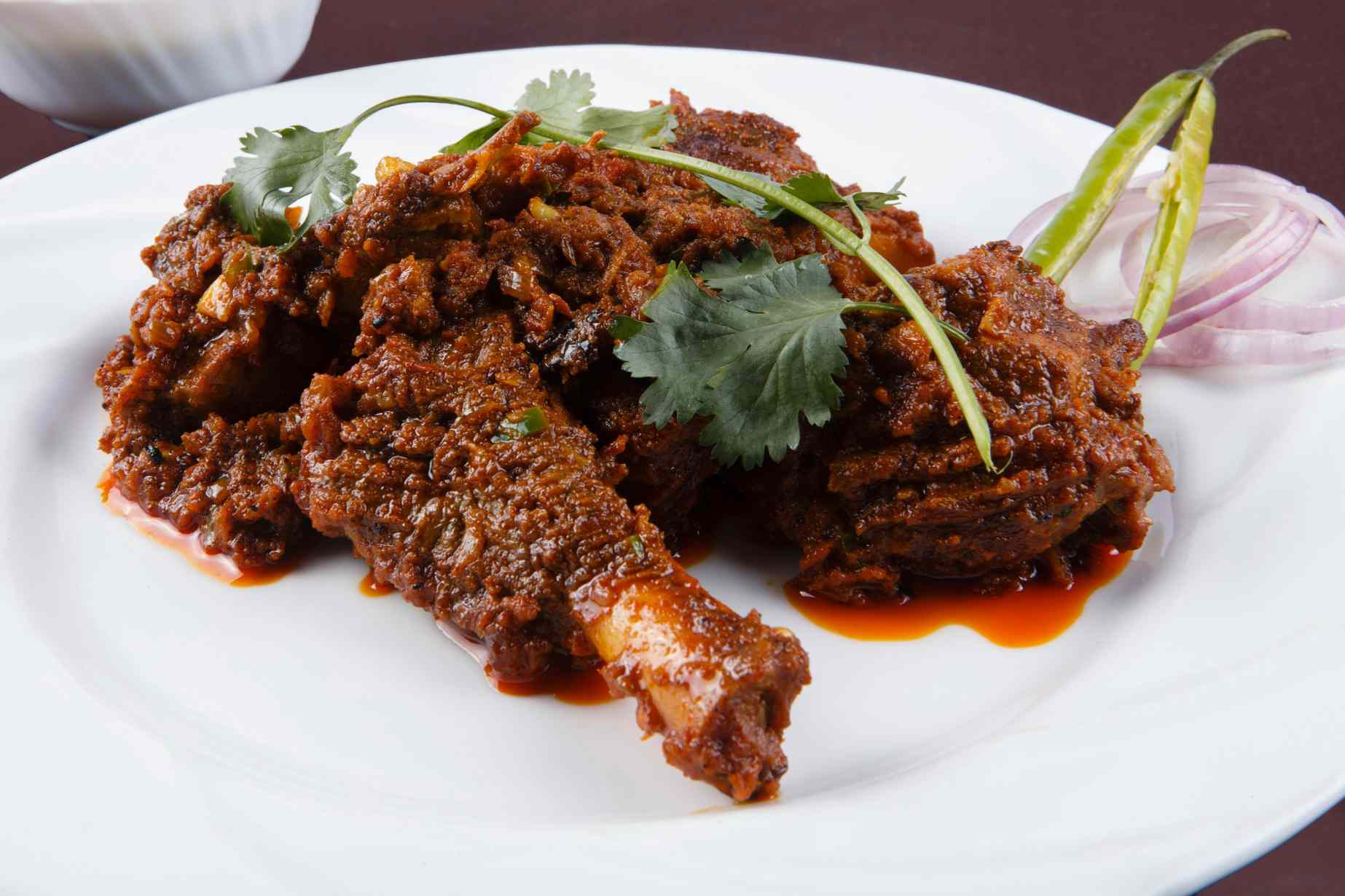 Mutton/goat curry garnished with a sprig of cilantro, a gree pepper and a few slices of onion