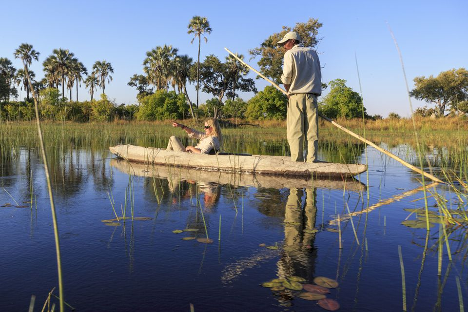 Tourist and guide in a mokoro canoe in the Okavango Delta