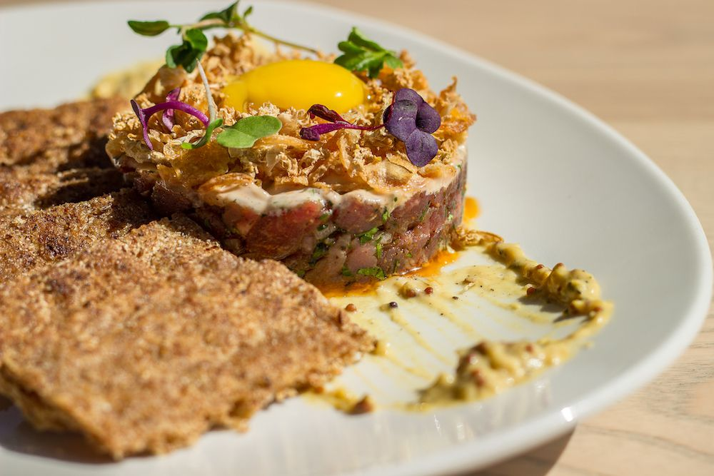 Tuna tartare topped with an egg yolk and served with brown crackers