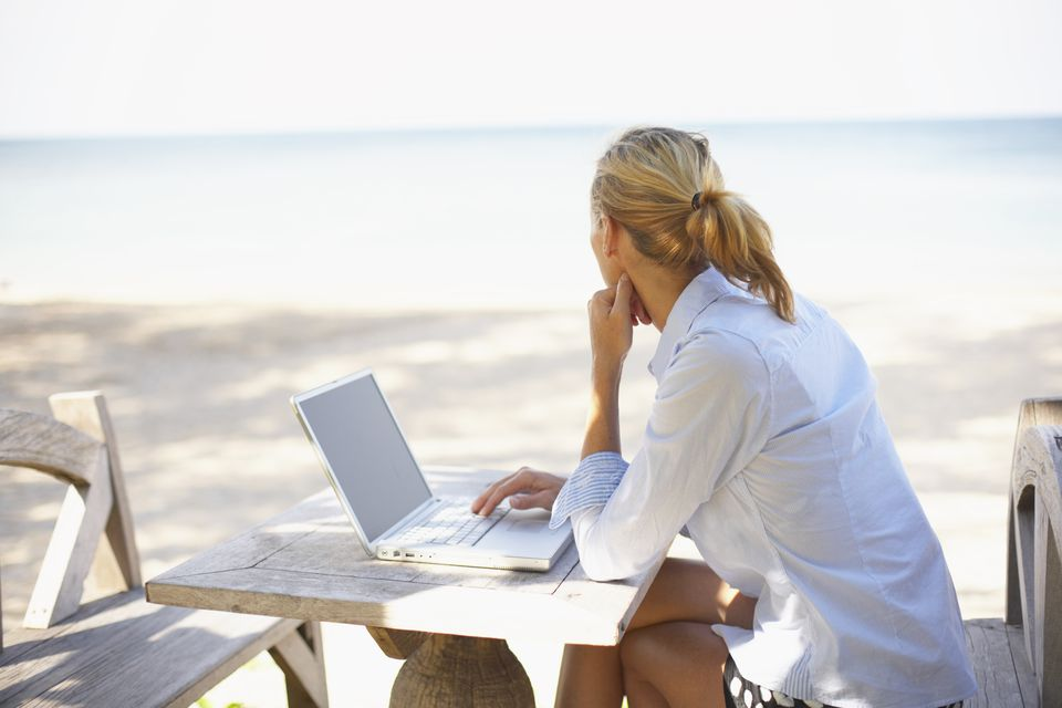 Mujer joven en la playa usando laptop