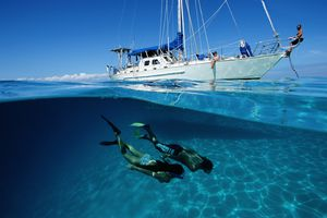 Two snorkelers dive under the water with a yacht in the background