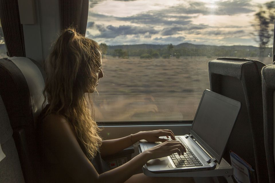 A woman works on her laptop while traveling on a train.