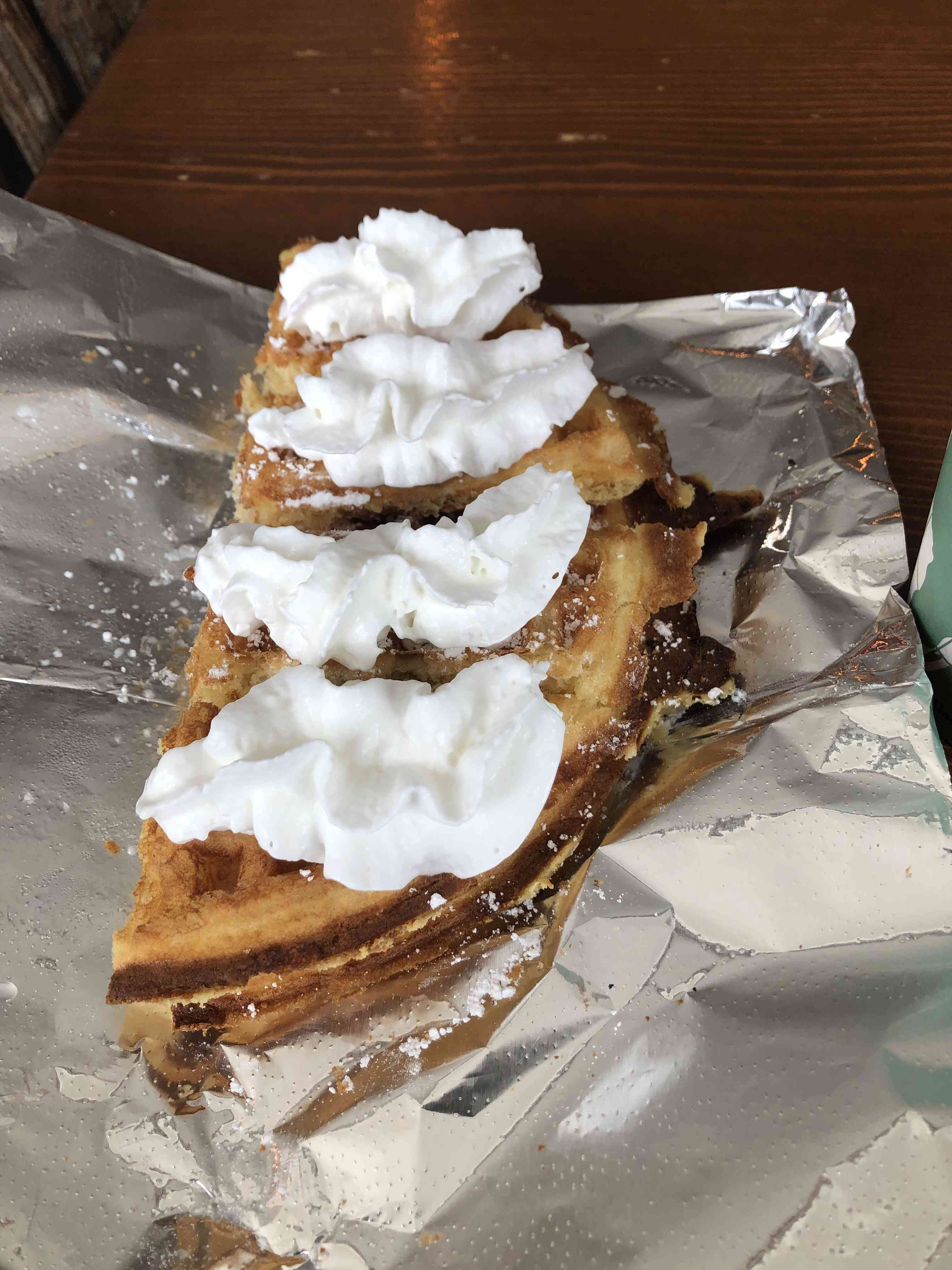 Waffle Folded in hal with four dollops of whipped cream on a sheet of aluminum foil