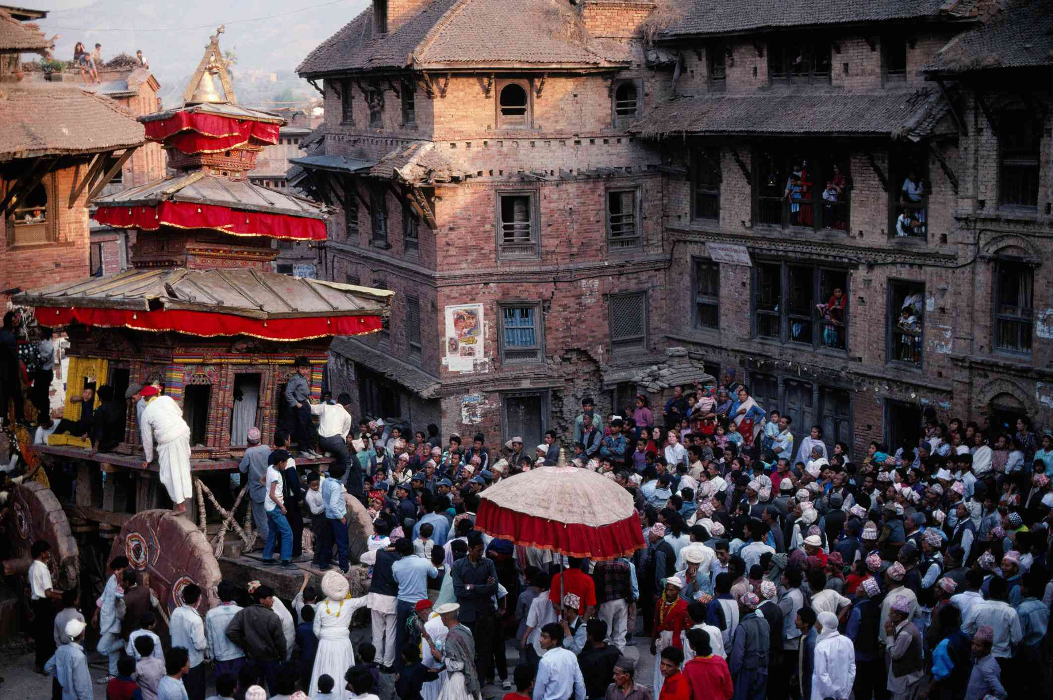 crowd of people standing around a wooden pagoda chariot with brick buildings behind