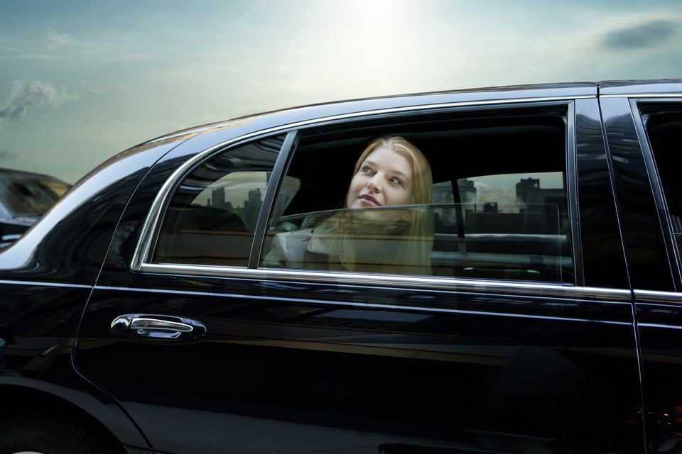 Woman looking out window of a limo at the city.