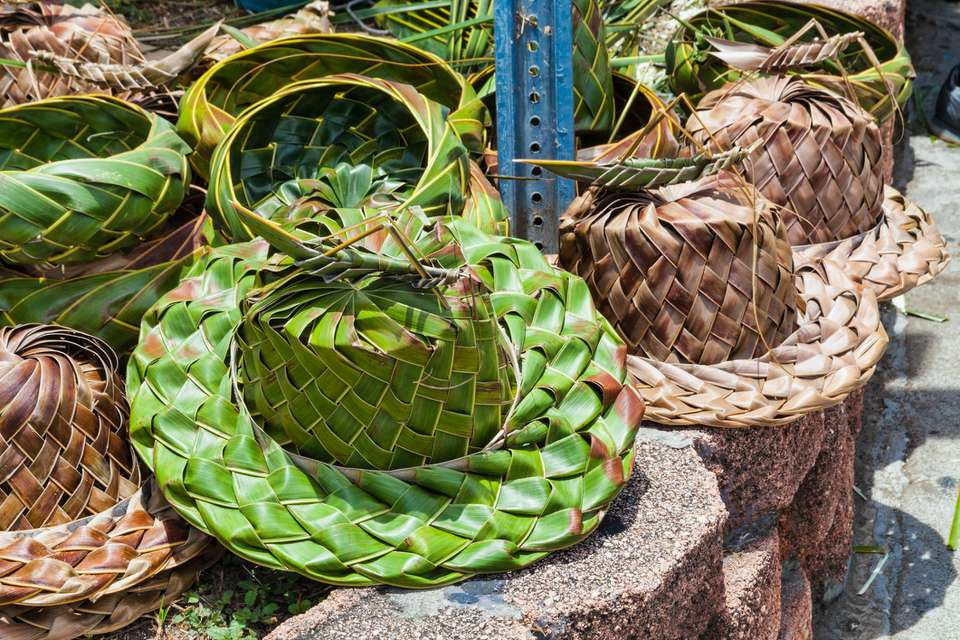 A pile of green and tan Palm frond hats