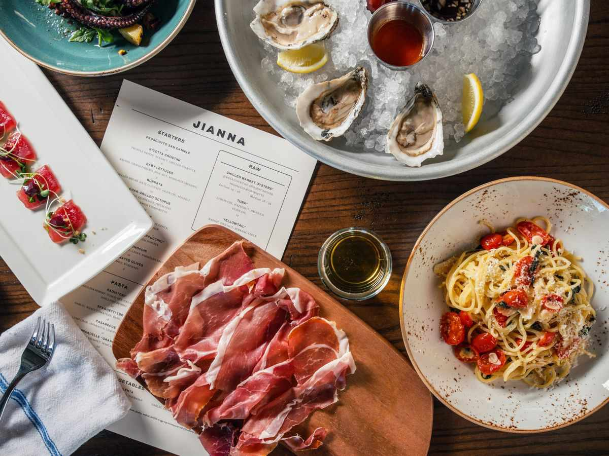 restaurant dining table with oysters, cured hams, and pasta