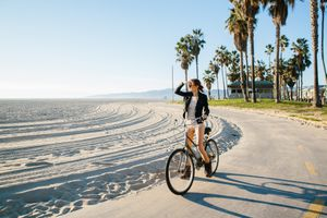 Young woman cycling at beach looking out to sea, Venice Beach, California, USA