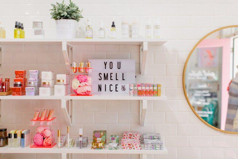 Estantes flotantes blancos en una pared blanca con productos rosados