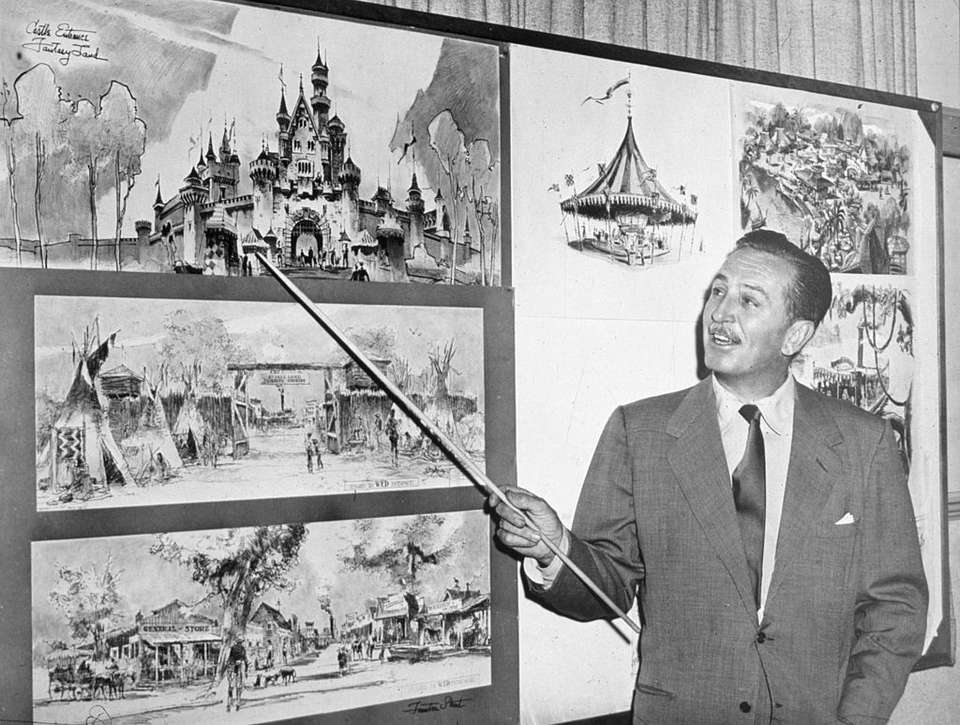 Walt Disney uses a baton to point to sketches of Disneyland, 1955