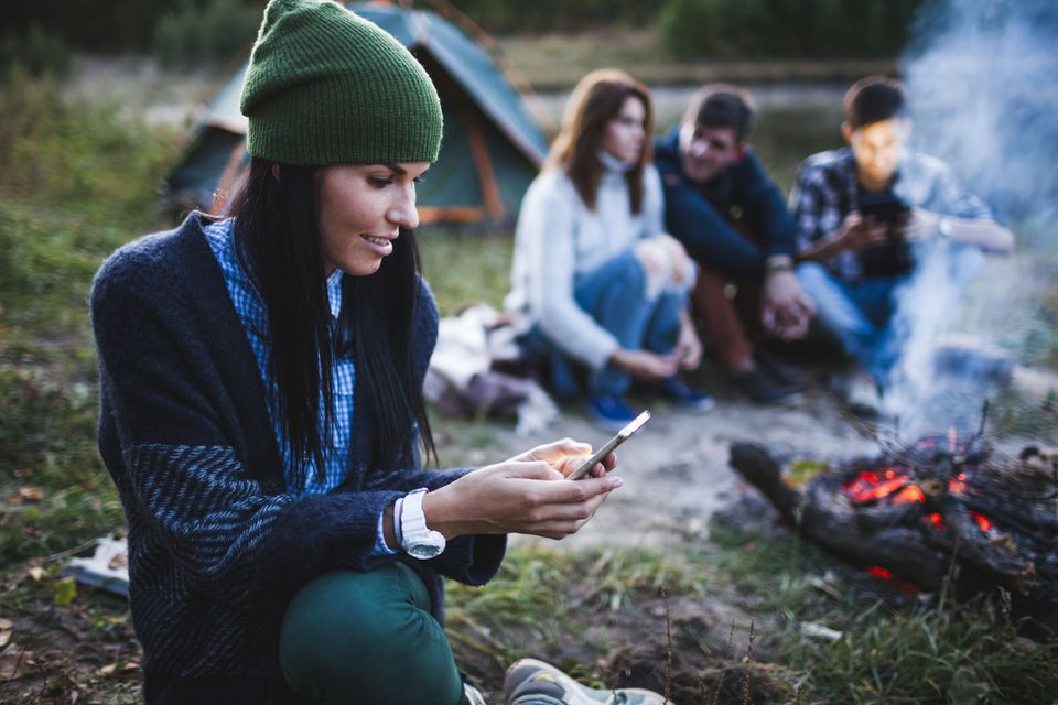 Young woman using mobile phone while friends sitting by bonfire at campsite