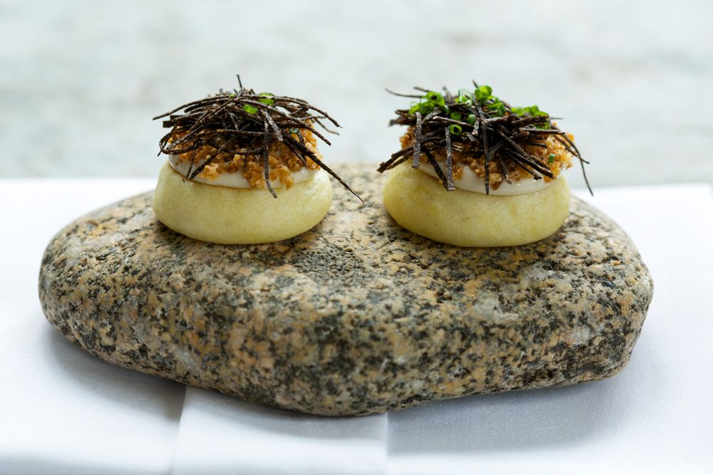 Two small appetizers on a speckled rock at the Ledbury