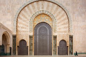 Man walking past one of the ornate gateways to Hassan II Mosque, Casablanca