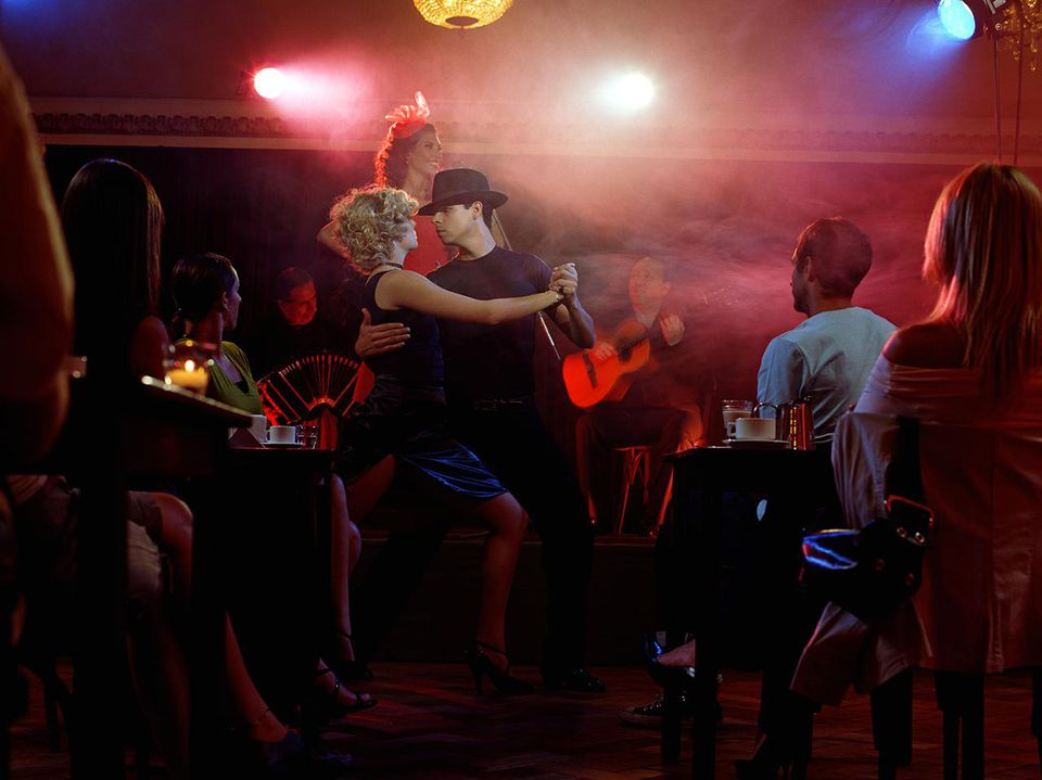 Young couple dancing tango for audience in restaurant