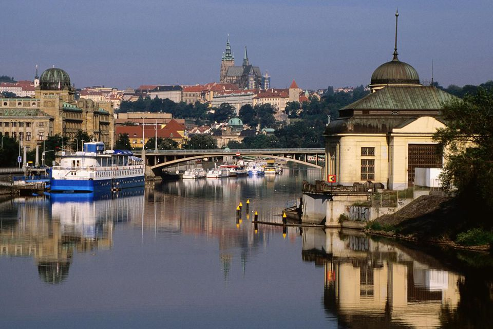 Old waterworks building on Stvanice Island, Svermuv Bridge, Botel Albatros and Prague Castle along Vlatva River.