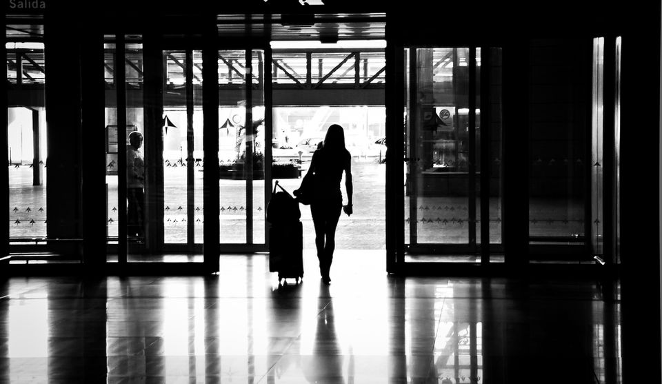 woman standing in airport entry way with luggage