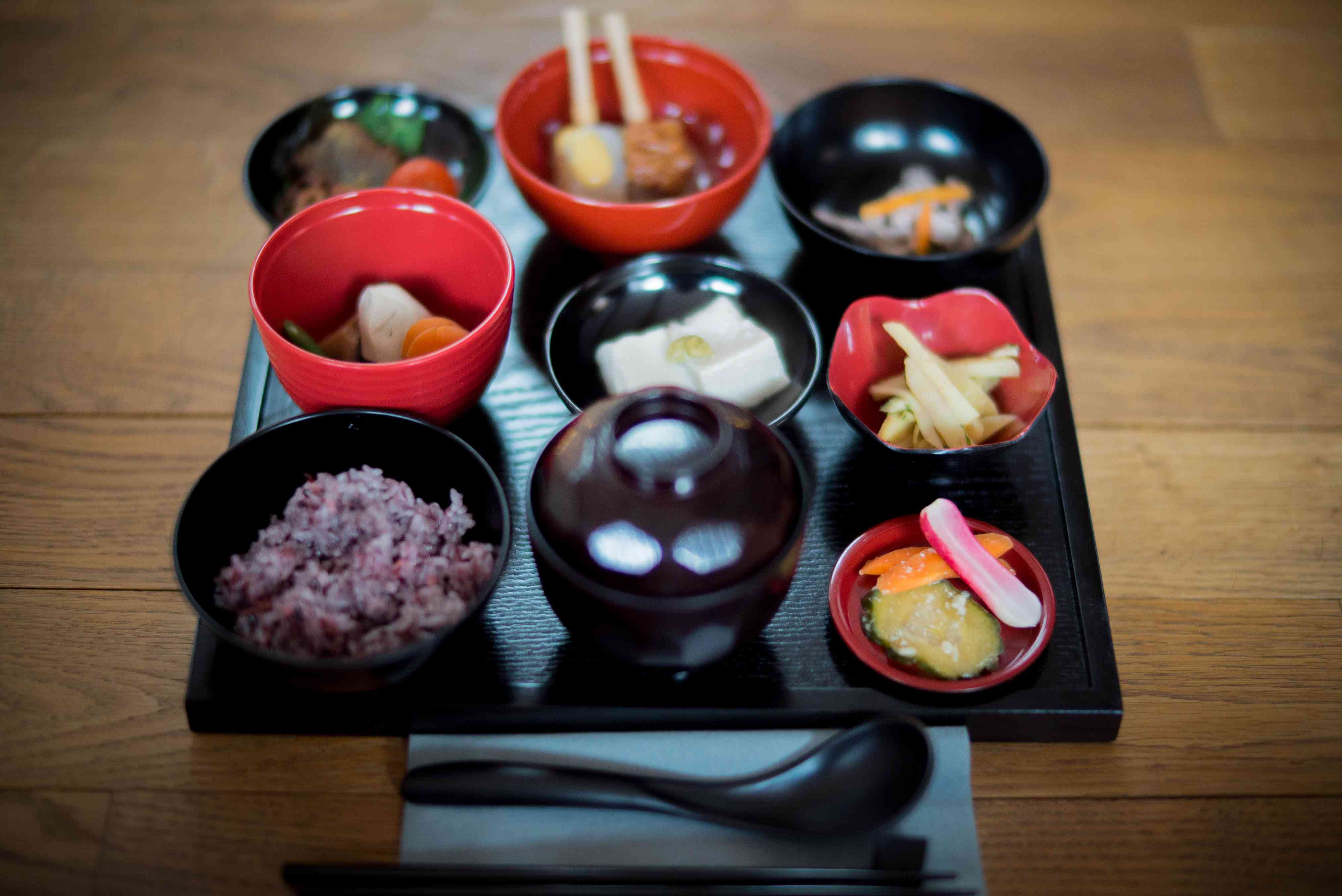 9 small plates of different dishes on a wooden square