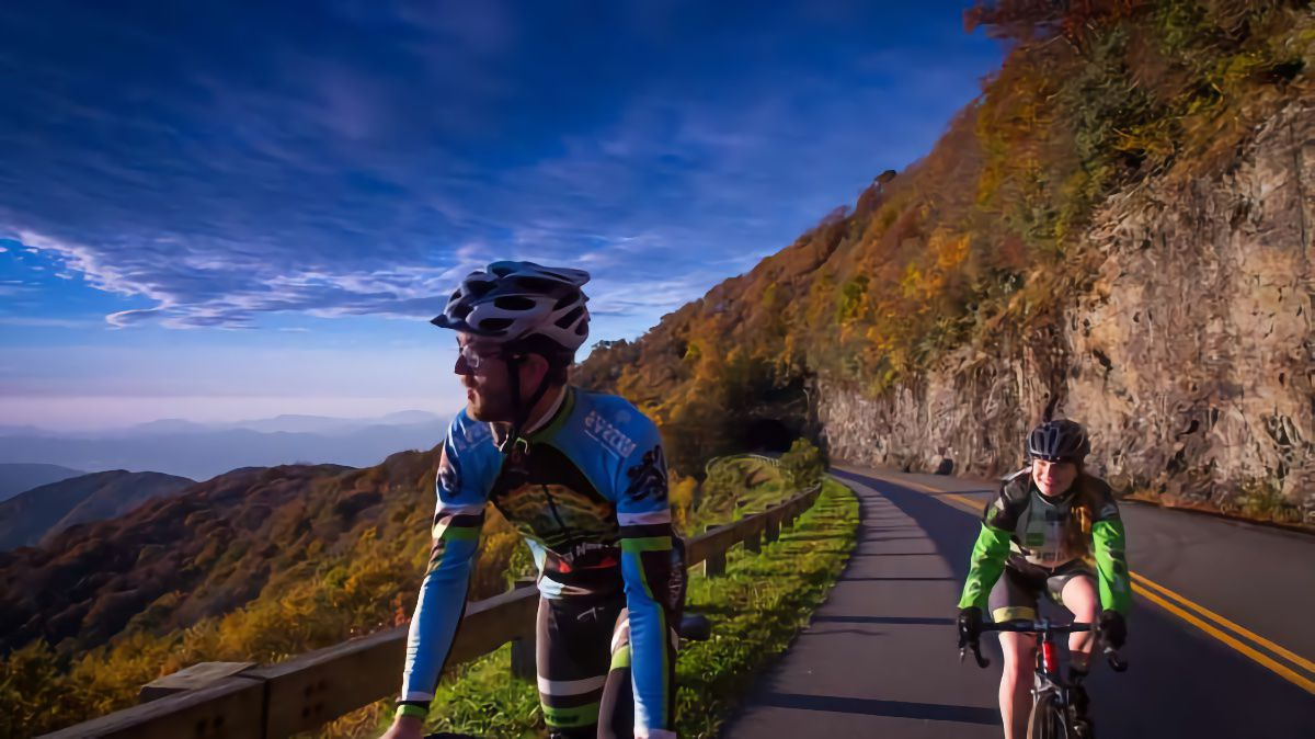 A male and female cyclist ride along a scenic mountain road with a tunnel in the background