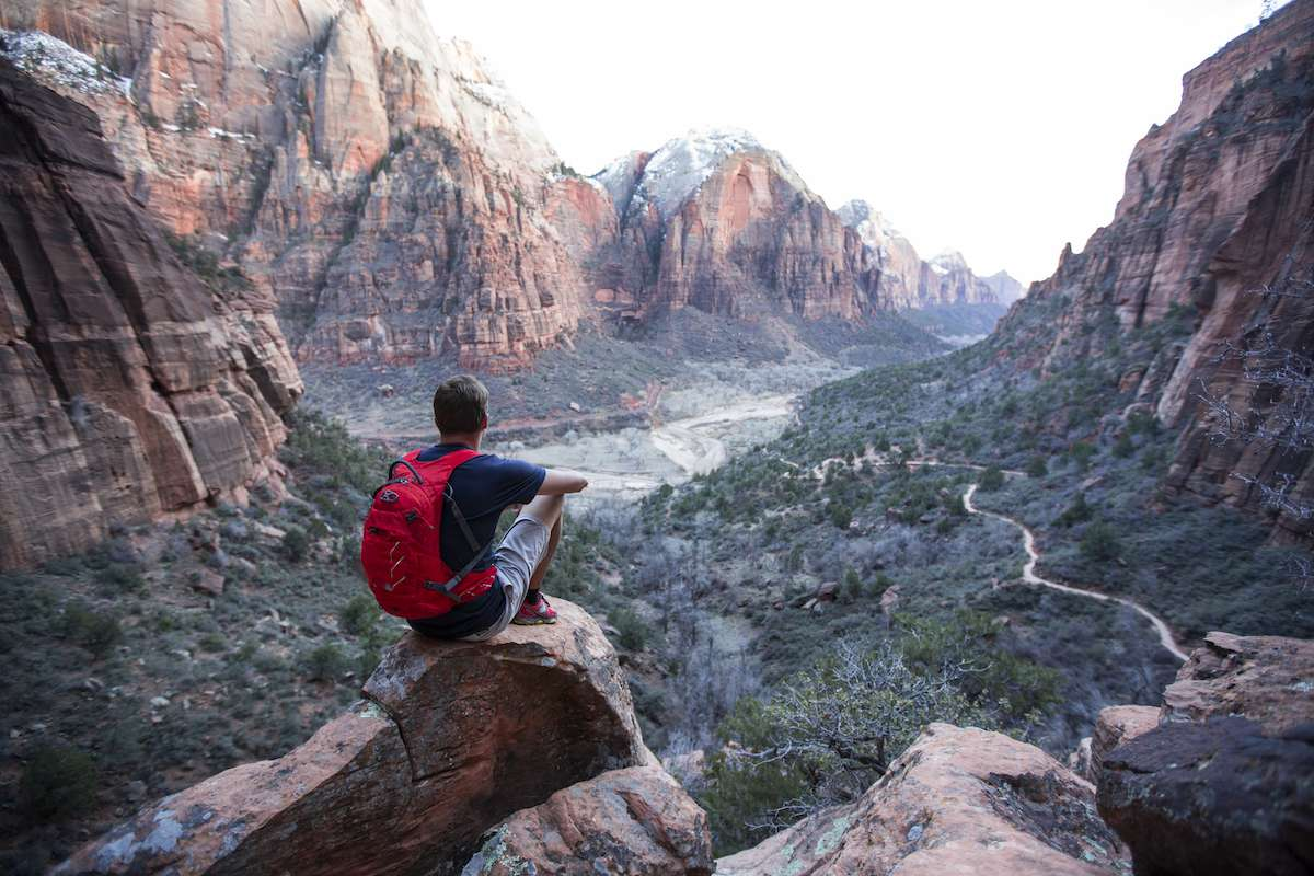 A man with a red backpack sets on a rock overlooking the massive Zion Canyon