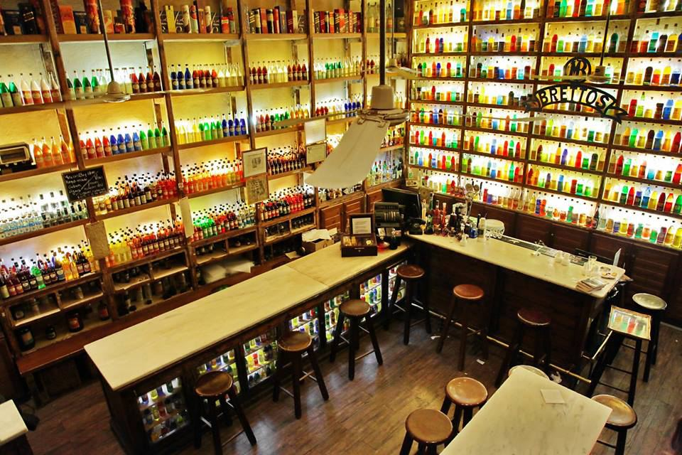 Inside of Brettos Plaka with walls of liquor bottles filled with colorful liquids. There are several long tables with wooden stools