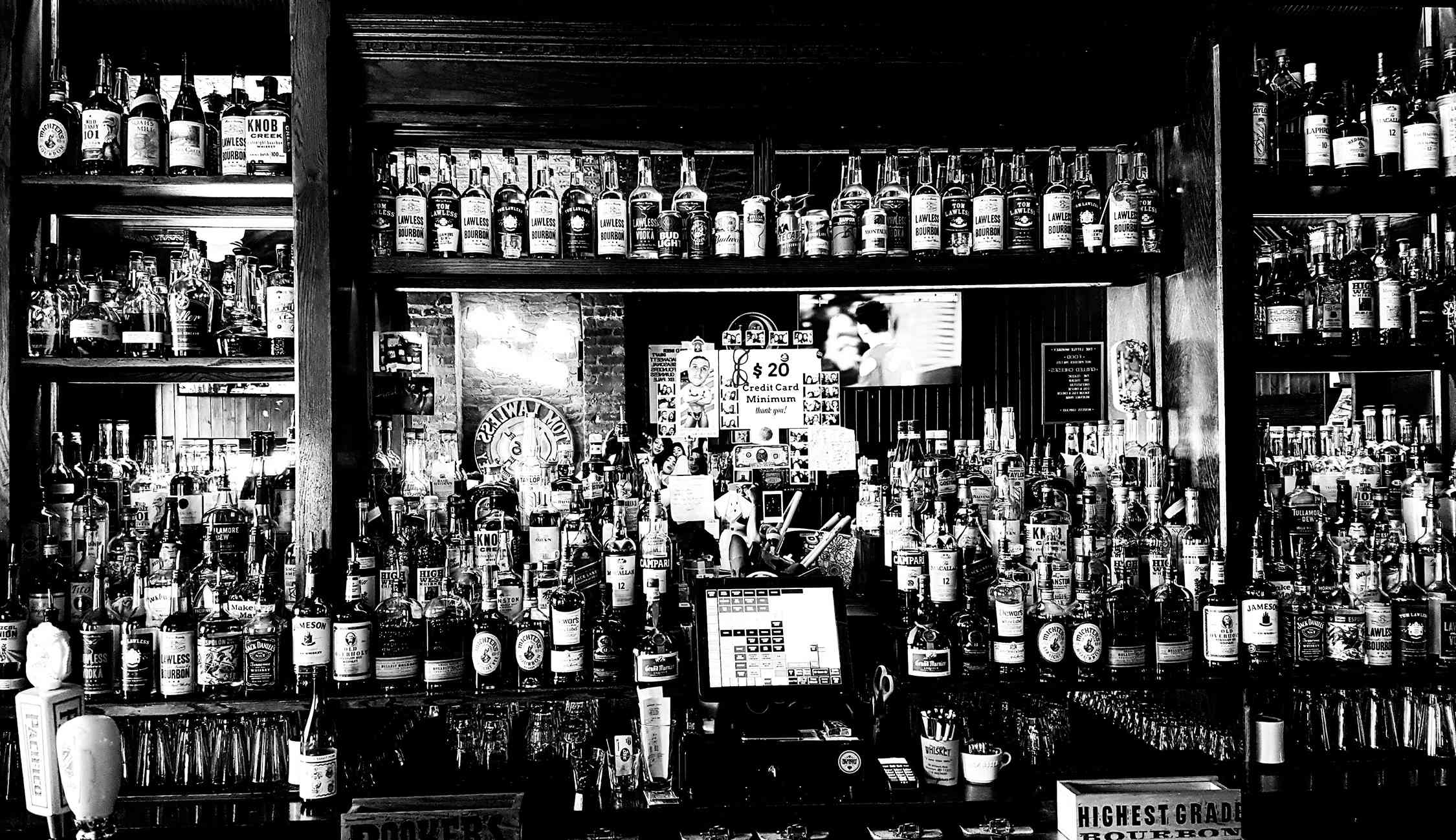 black and white image of the liqour bottles at Little Whiskey Bar