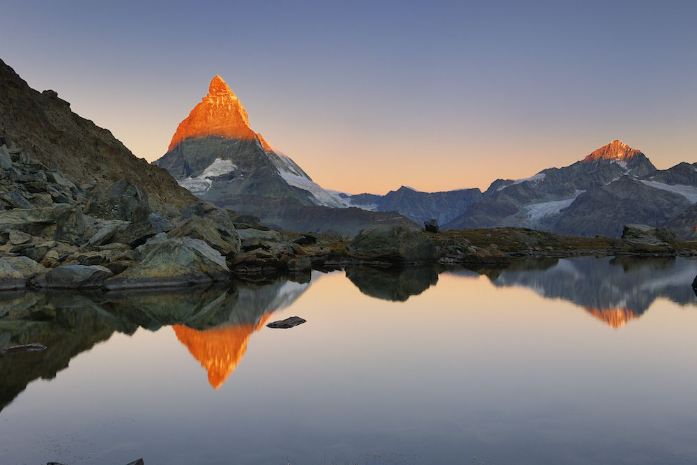 A towering and jagged peak reflects on a mountain lake at sunset