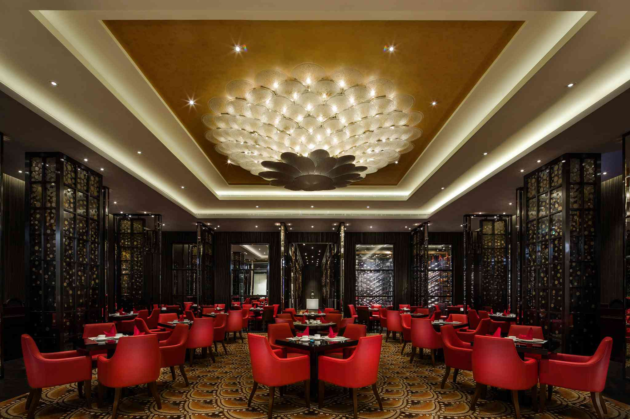 Dining room at the Parisina Macao with red chairs and black wall decorations