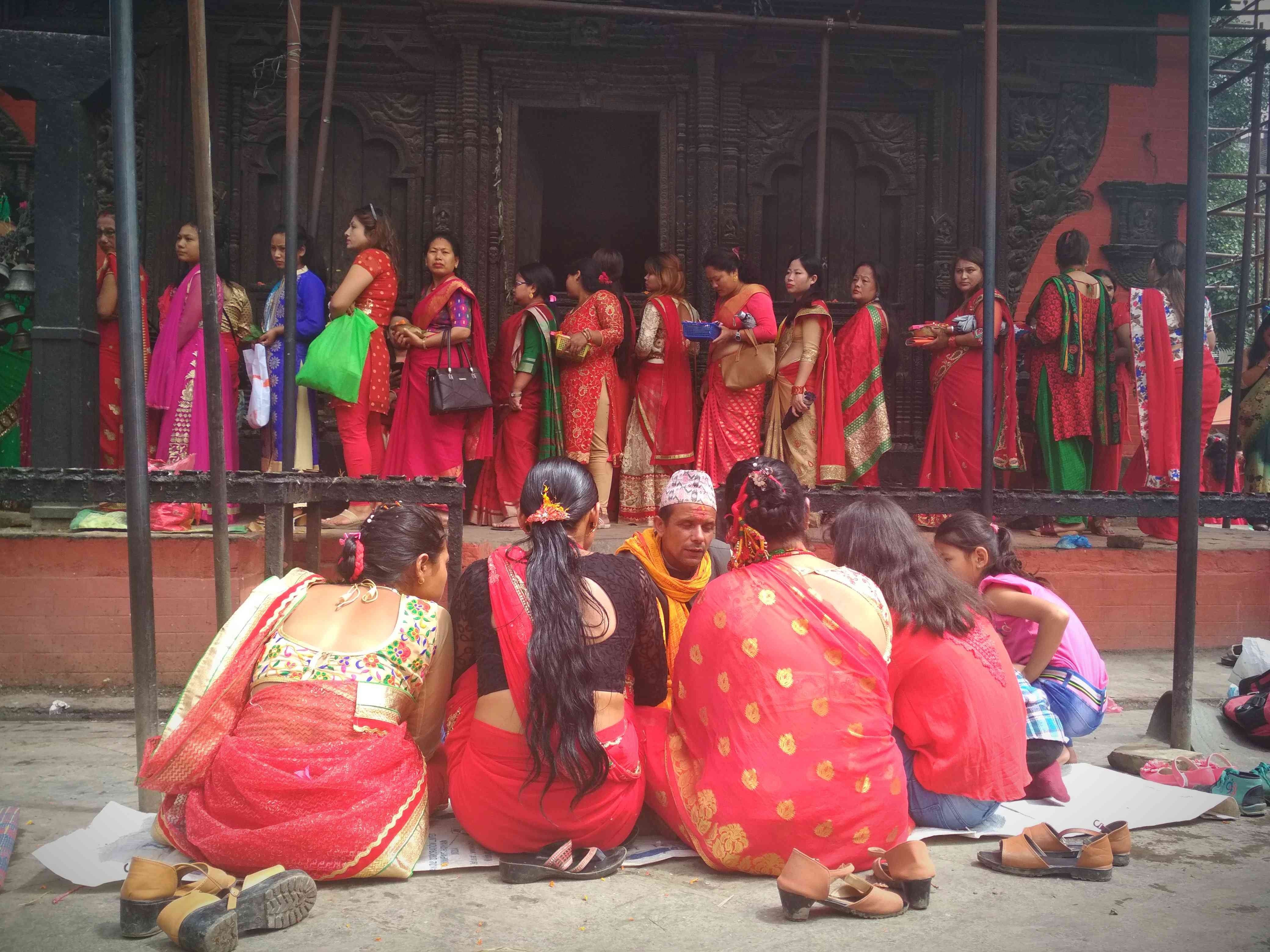 women wearing red saris lined up at a temple and seated on the ground
