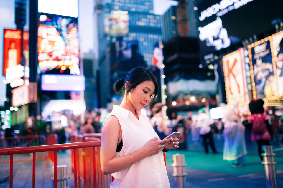 Young woman reading message on smart phone in Time Square, New York