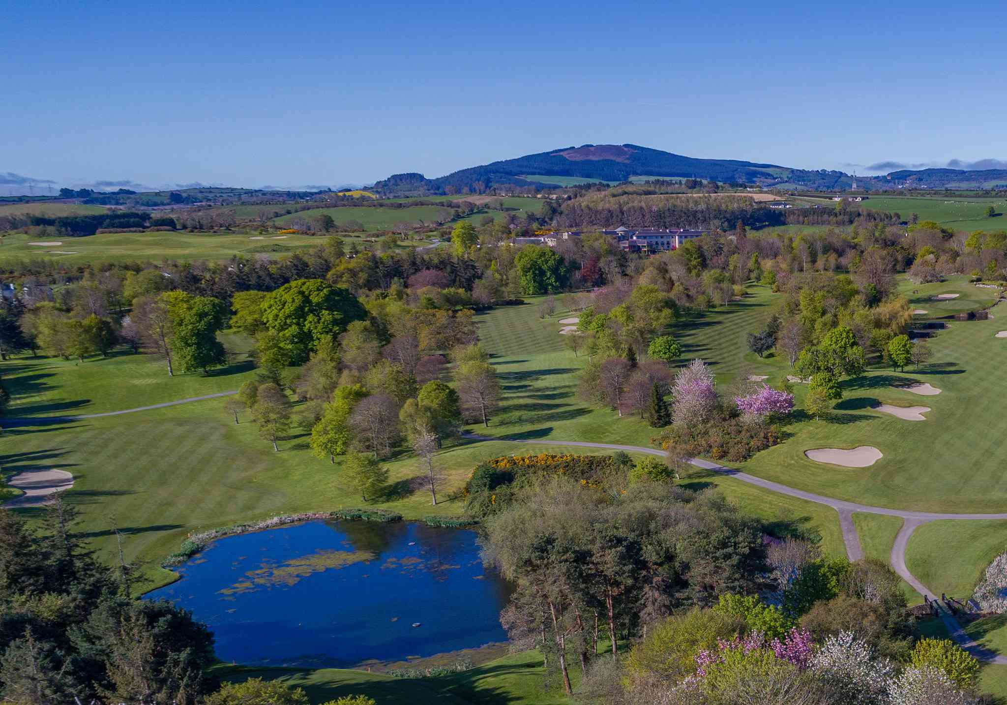 Arial shot of golf course with greens, water and trees