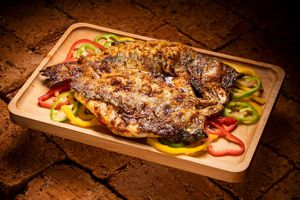 Whole grilled fish, butterflied, on a bed of sliced bellpeppers