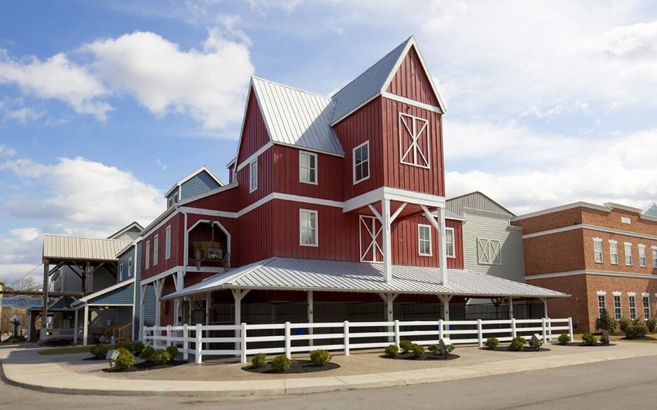 Red, three story barn-style building with gray roofs and a white fence