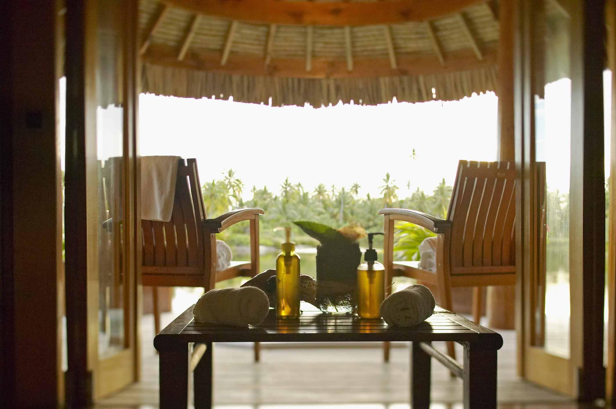 Interior del spa, mirando más allá de las mesas y sillones en un entorno tropical