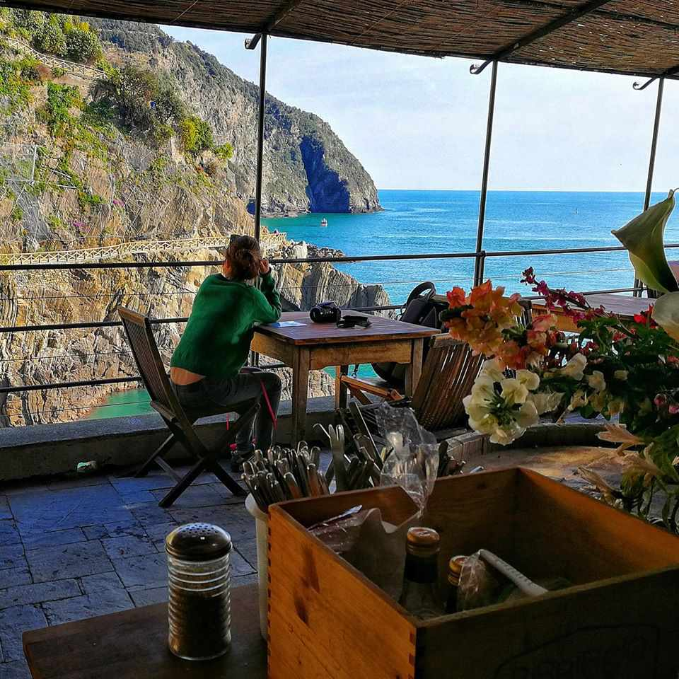Woman sitting at a table in a restaurant terrace looking at the cliffs and waters of riomaggiore