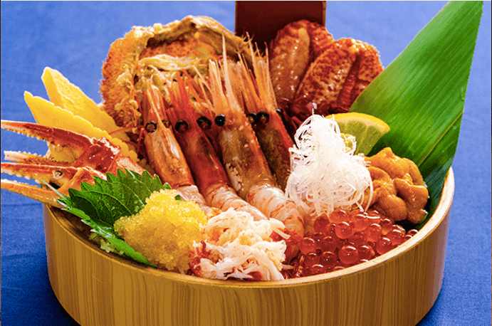 bamboo tray with an assortment of seafood and sesame and bamboo leaves as decoration