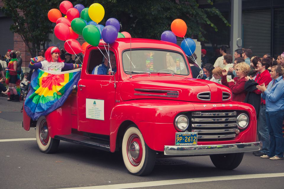 Portland gay pride participants ride in a bright red vintage classic pickup truck covered in balloons.