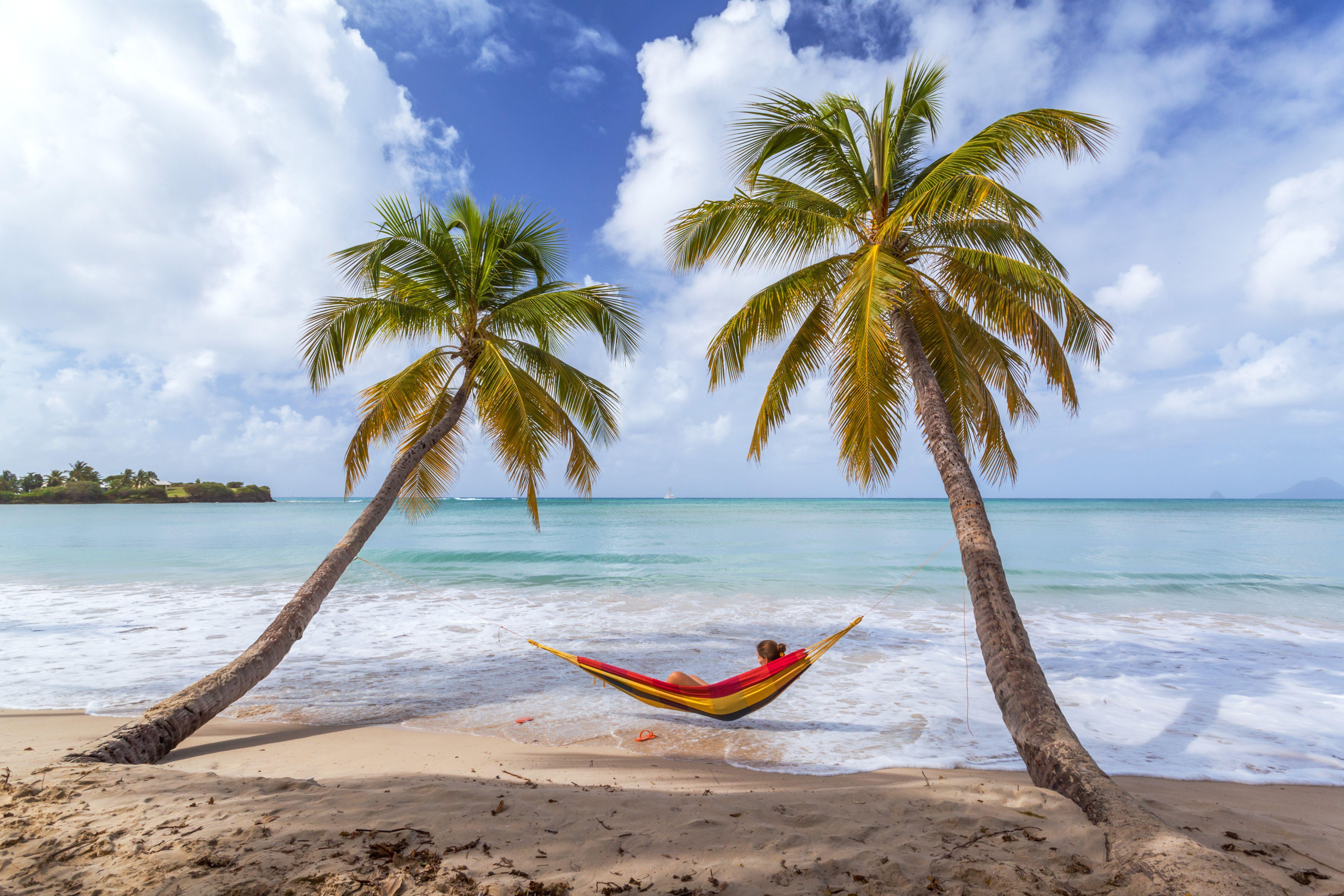 Woman lying on hammock between palm trees at beach