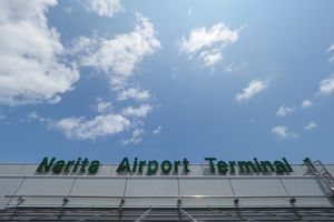 outside of Narita airport terminal 1 in Japan with a bright sky
