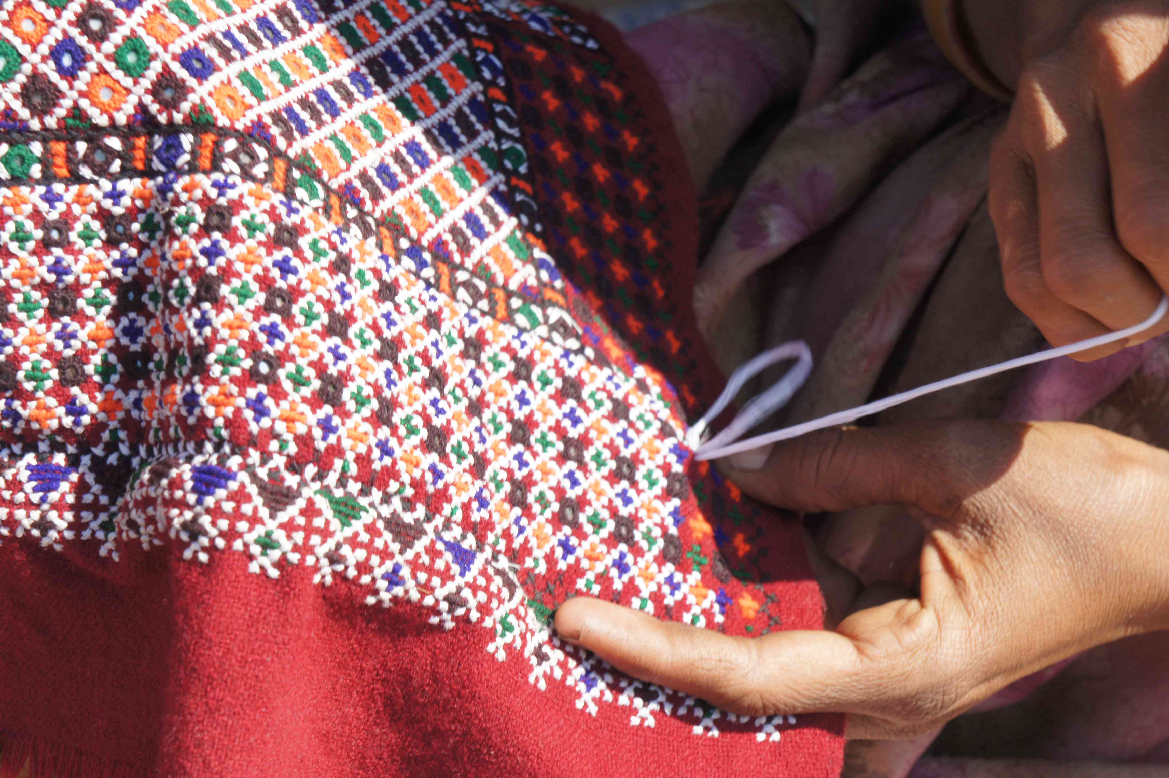 Close up of hands embroidering a scarf in Kutch