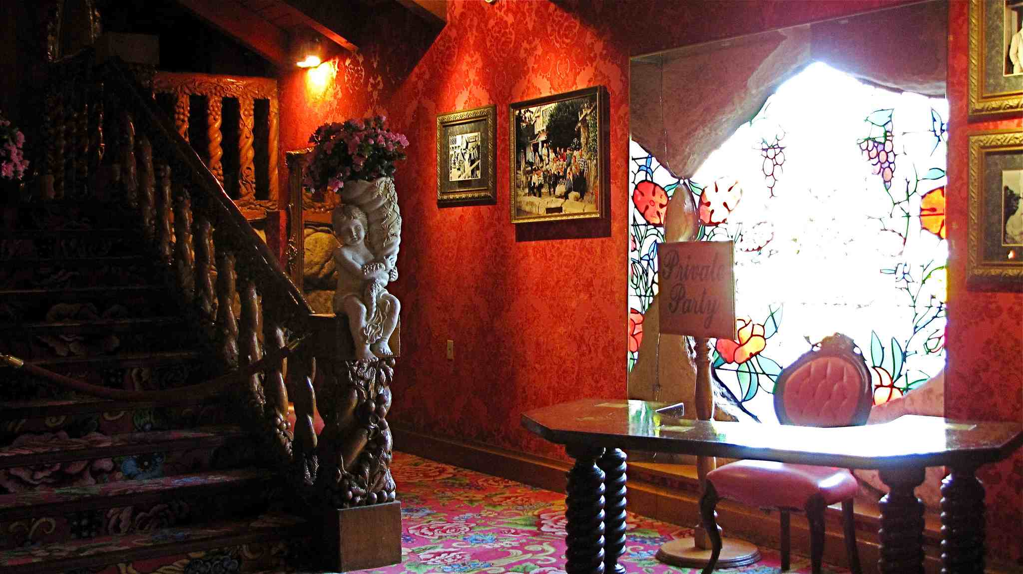 Interior shot of a red room with a stained glass windowat the Madonna Inn