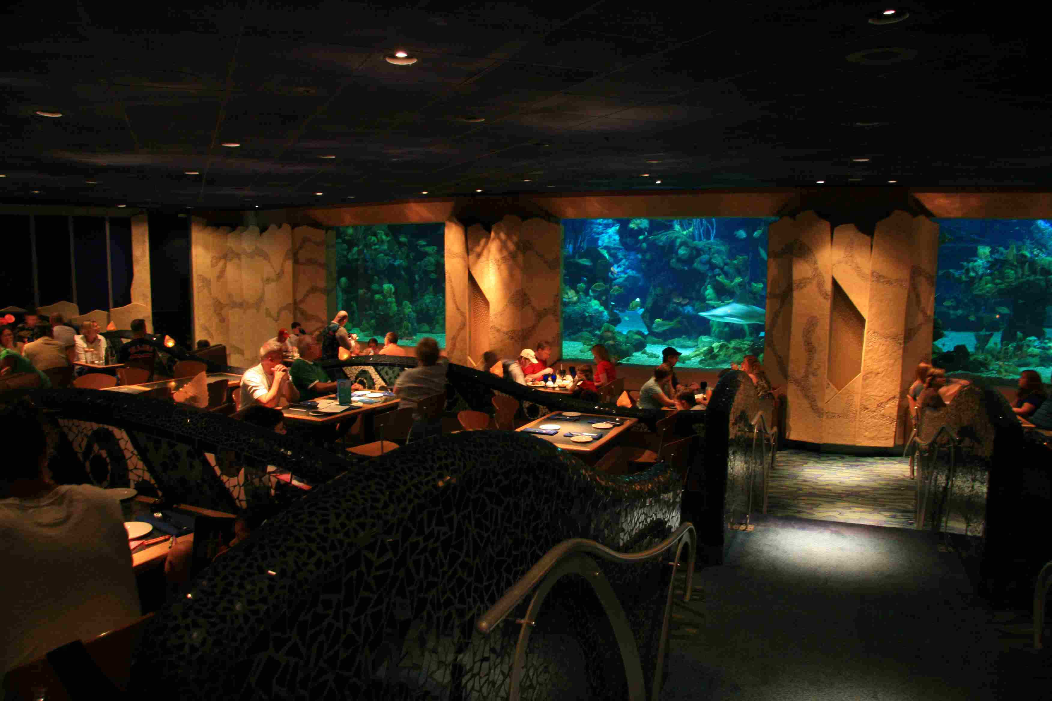 Diners at Coral Reef Restaurant eat with views of the massive saltwater tank at Epcot