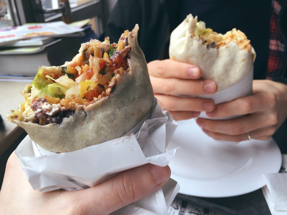 Cropped hands holding burrito in restaurant.