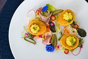 3 Deep fried deviled eggs garnished with flowers and greens, and charcuterie on a white plate