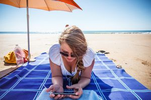 Woman using cell phone at the beach