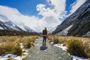 person wearing yellow jacket and black backpack walks along a stony path with mountains and clouds around