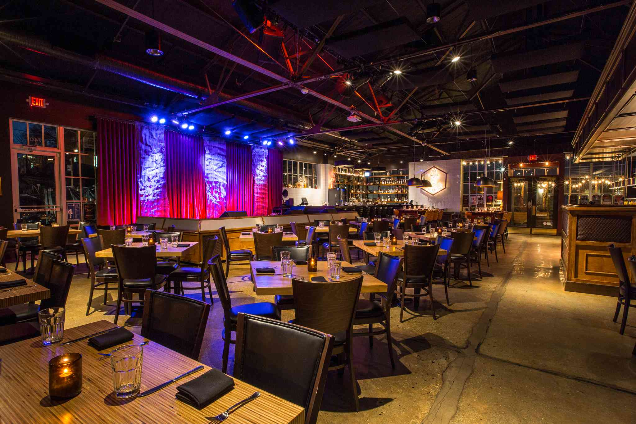 Interior of Venkman's in Atlanta. There are dozens of four top tables and a medium sized stage with a curtain behind on on the back wall
