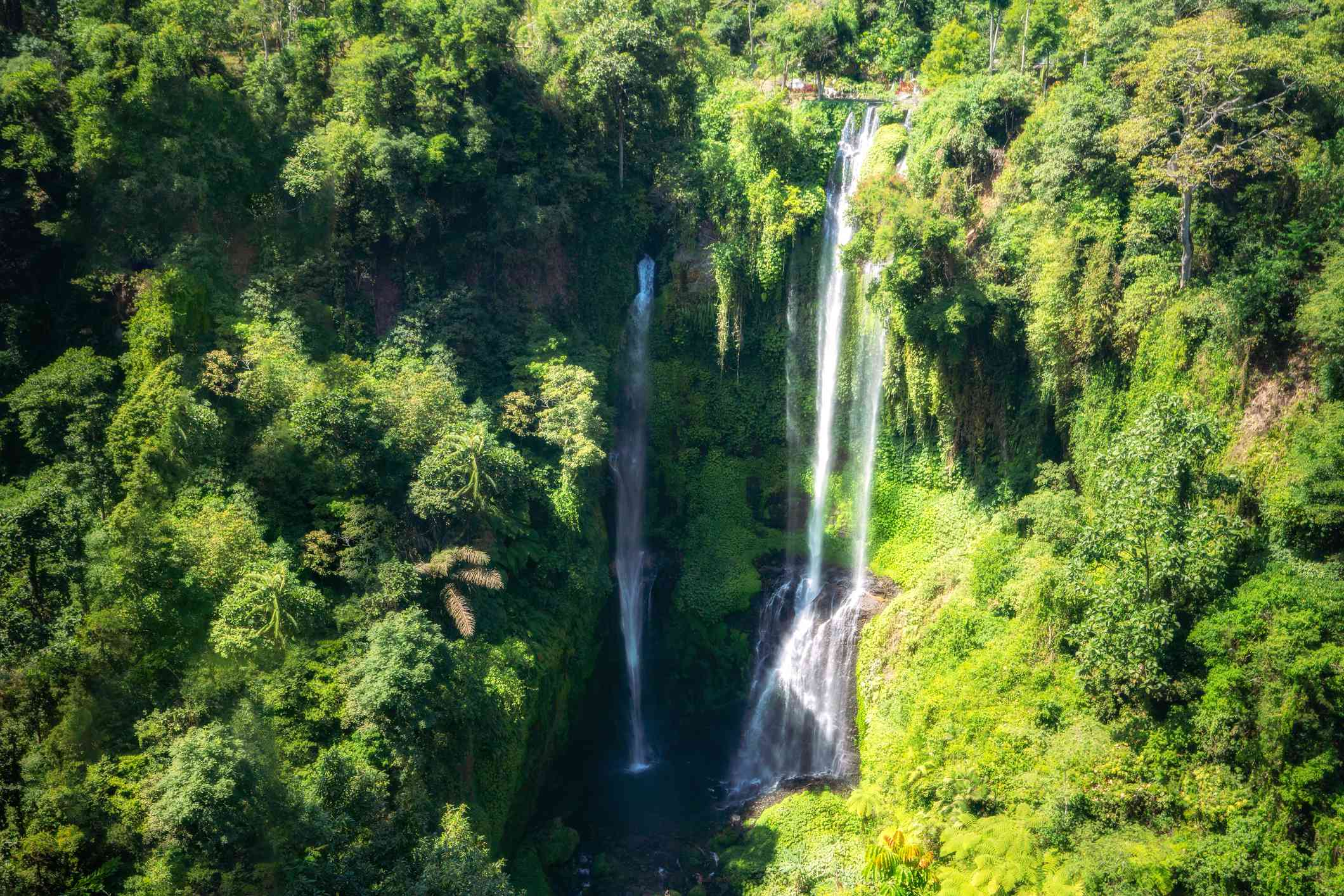 Tropical waterfall view at Sekumpul waterfall in green forest from high view point in Bali island, Indonesia. Embracing the beauty in nature travel nature concept.
