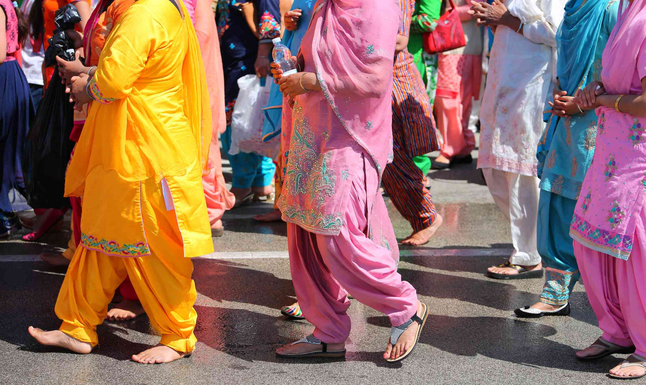 Barefoot Sikh women dressed in colorful traditional clothes