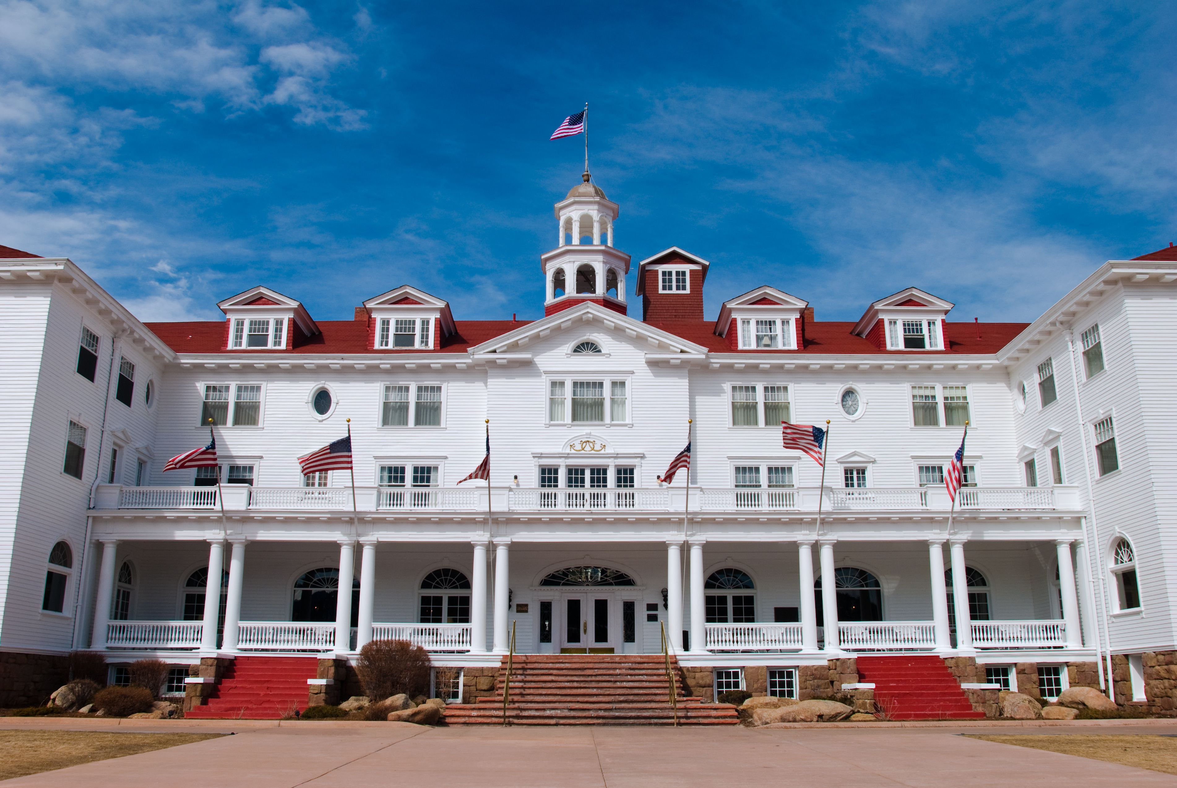 Wide-angle view of the Stanley Hotel in Estes Park, Colorado with a rich blue sky in the background.