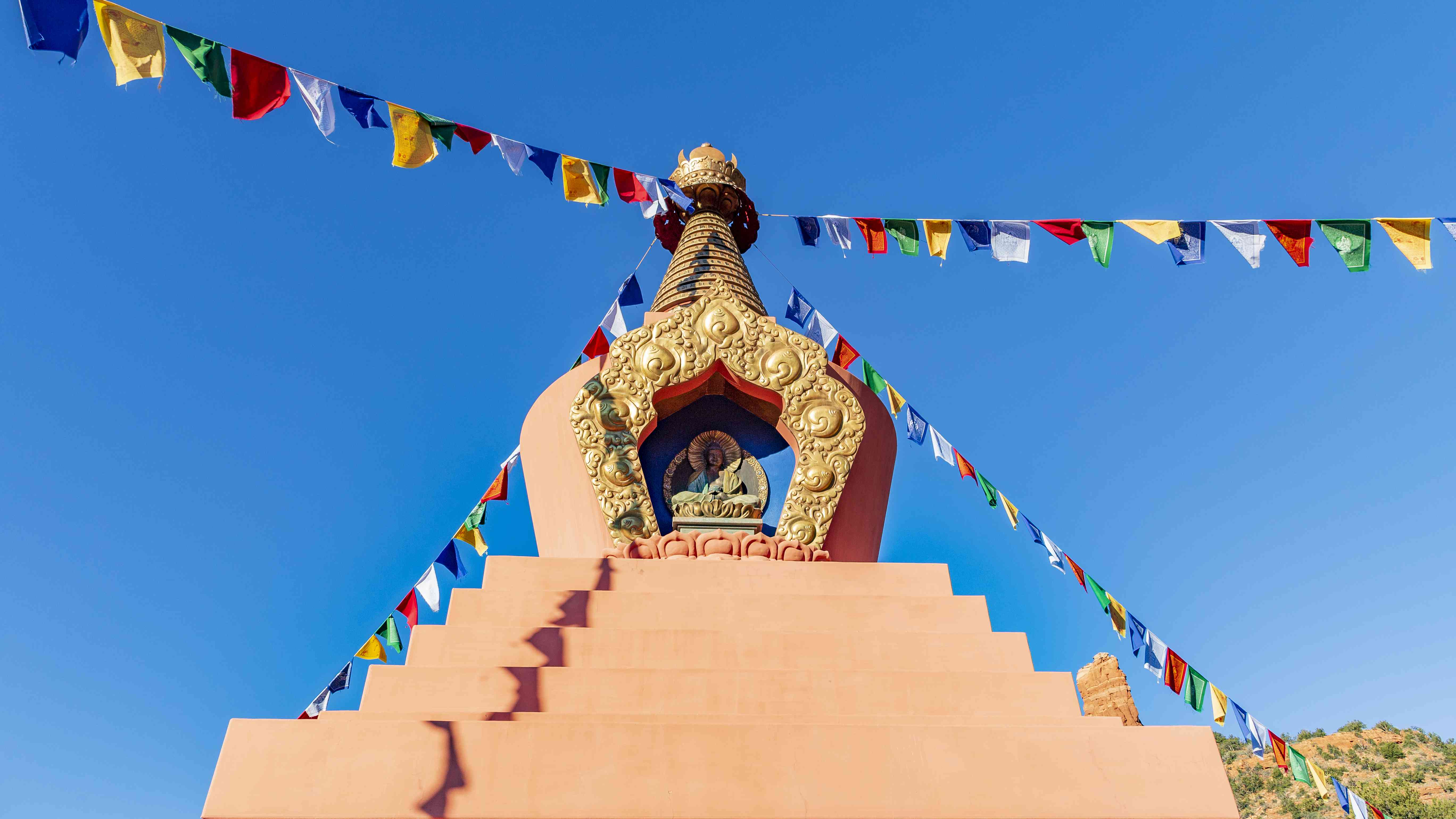 low angle view of a Buddhist stupa with colorful flags in Sedona, Arizona
